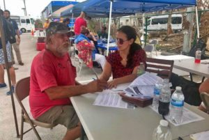 client and attorney talking under tent at outdoor hurricane relief clinic